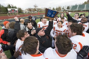 Hasbrouck Heights head coach Nick Delcalzo raises the trophy in celebration of the Aviators thrilling 13-7 victory over Shabazz in the North Jersey Section 2, Group 1 High School Football Final in Newark on Saturday. (Steve Hockstein | For NJ Advance Media)