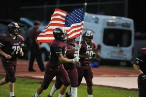 Phillipsburg's Tommy Coury carries the flag onto the field against Union. (Tim Wynkoop | lehighvalleylive.com contributor)