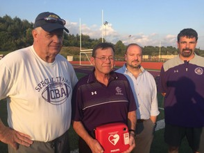 (Left to right) Joe Reagan, Randy Kinn, Rich Tallarico and Mike Picciano teamed to treat a CBA football player who collapsed on the field during a game Sept. 14. Kinn, the team's trainer, is holding the automated external defibrillator that re-started the player's heart.