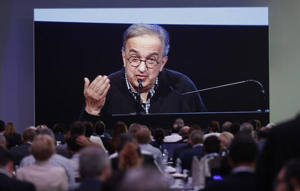 Journalists watch a giant screen as Fiat Chrysler CEO Sergio Marchionne speaks during the 'Capital market day' at the FCA headquarters in Balocco, Italy, Friday, June 1, 2018. Fiat Chrysler CEO Sergio Marchionne is outlining his business plan for the automaker's next five years in his last big presentation to investors before retiring next year.