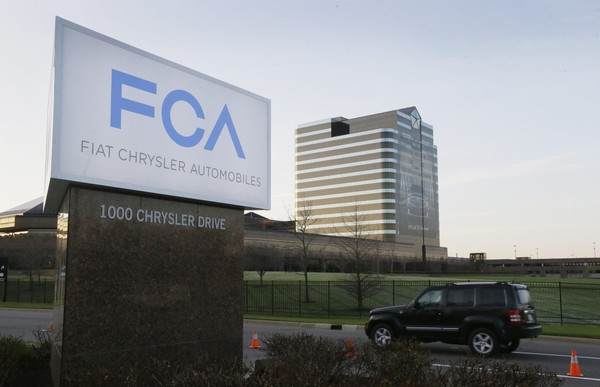 FILE - In this Tuesday, May 6, 2014, file photo, a vehicle moves past a sign outside Fiat Chrysler Automobiles world headquarters in Auburn Hills, Mich. Fiat ChrysleraEUs existing streak of 75 straight months of sales gains should have ended in 2013, according to revised sales figures released by the automaker Tuesday, July 26, 2016. The revision comes as two federal agencies investigate whether the company inflated sales by pressing dealers to buy more vehicles. (AP Photo/Carlos Osorio, File) AP (Carlos Osorio)