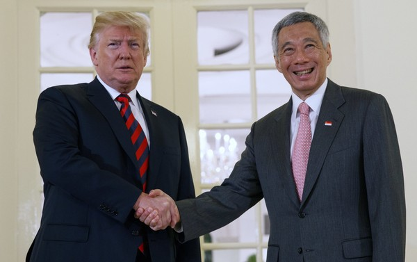 President Donald Trump shakes hands as he meets with Singapore Prime Minister Lee Hsien Loong ahead of a summit with North Korean leader Kim Jong Un, Monday, June 11, 2018, in Singapore.