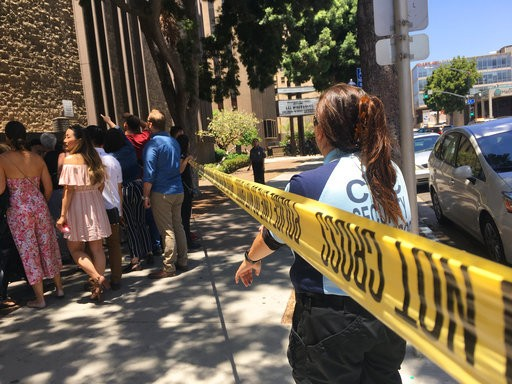 Theatergoers wait in line behind police tape outside the San Diego Civic Theatre, Sunday, June 3, 2018, in San Diego, near the area where a police officer accidentally shot himself in the leg while pursuing a hit-and-run suspect.