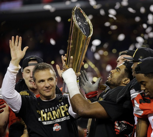 This Jan. 12, 2015, file photo shows Ohio State head coach Urban Meyer and Ezekiel Elliott celebrating after the NCAA college football playoff championship game against Oregon, in Arlington, Texas. Meyer will retire after the Rose Bowl, the university announced on Dec. 4, 2018. (AP Photo/Eric Gay, File)
