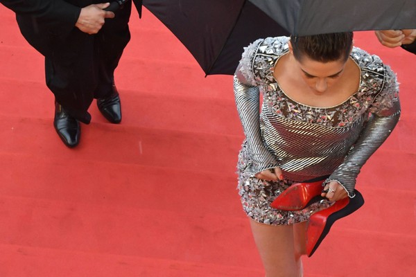 "Actress and member of the Feature Film Jury Kristen Stewart walks barefoot on the red carpet after she removed her shoes on May 14, 2018, for the screening of the film ""BlacKkKlansman"" at the 71st edition of the Cannes Film Festival. (Antonin Thuillier/AFP/Getty Images)"
