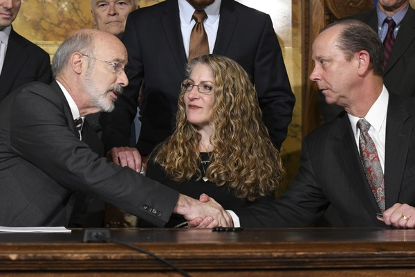Pennsylvania Gov. Tom Wolf shakes hands with Jim Piazza after signing anti-hazing legislation inspired by Piazza's son, Penn State student Tim Piazza, who died after a night of drinking in a fraternity house, Friday, Oct. 19, 2018 in Harrisburg. Sitting between them is Evelyn Piazza, the mother of Tim Piazza. (AP Photo | For NJ Advance Media)