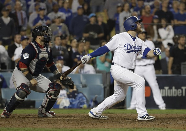 Los Angeles Dodgers' Max Muncy watches his walk off home run during the 18th inning in Game 3 of the World Series baseball game to defeat the Boston Red Sox 3-2 on Saturday, Oct. 27, 2018, in Los Angeles. Left is Red Sox catcher Sandy Leon. (AP Photo/David J. Phillip)