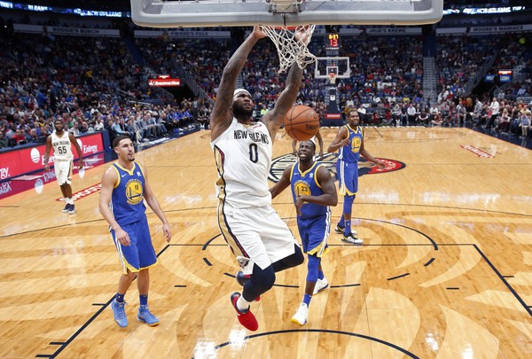 New Orleans Pelicans center DeMarcus Cousins (0) dunks in front of Golden State Warriors forward Draymond Green (23) and guard Klay Thompson (11) in the first half of an NBA basketball game in New Orleans, Monday, Dec. 4, 2017. (AP Photo/Gerald Herbert, File)