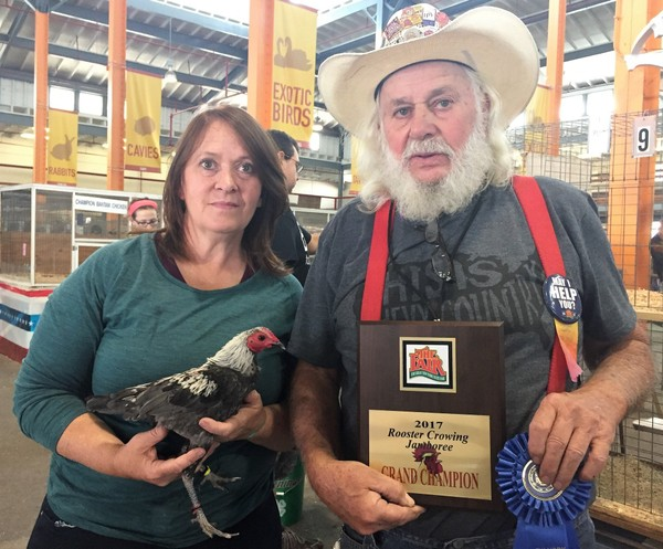 Kelleejean Lounsberry holds the winning bird from the Championship Rooster Crowing Contest at the New York State Fair. Her father Lou Smith, who also competed in the finals, holds her championship plaque and blue ribbon. Sept. 4, 2017.