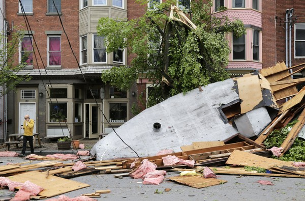 A man walks past damage caused by a storm in Newburgh, N.Y., Wednesday, May 16, 2018. Powerful storms pounded the Northeast on Tuesday with torrential rain and marble-sized hail, leaving thousands of homes and businesses without power. (Seth Wenig | AP Photo)