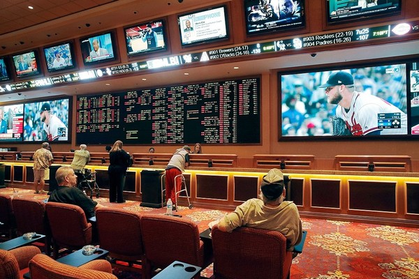 Bettors place wagers in the sports book at the South Point hotel and casino in Las Vegas. New York officials are trying to set the rules to allow sports betting. (John Locher)