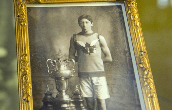 In this photo taken on June 14, 2014, World War I soldier and 1907 Boston Marathon winner Tom Longboat is framed behind glass on exhibit at the In Flanders Fields Museum in Ypres, Belgium.(Virginia Mayo | AP)
