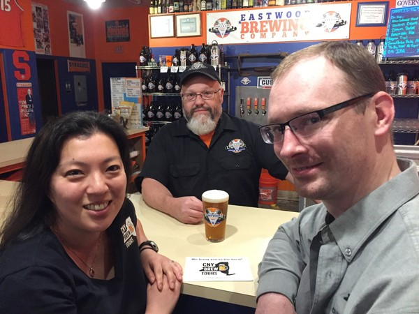 Lauren and Michael Braico, owners of CNY Brew Tours, stop in to Eastwood Brewing Co. in Syracuse and visit with owner Pete Kirkgasser (center).