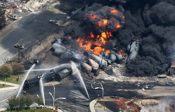 Smoke rises from railway cars carrying crude oil after derailing in downtown Lac-Megantic, Quebec, on July 6, 2013.