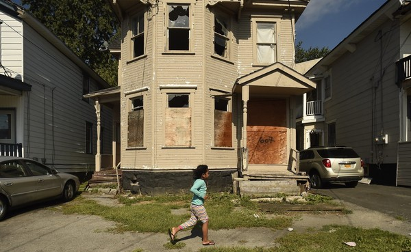 A little girl run past an abandoned house on Ash St on Syracuse's northside Aug. 25, 2015.