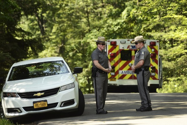 New York State Police block the entrance of Welch Road in Corning, N.Y., Monday, July 2, 2018, as they investigate the scene of a shooting in nearby Erwin. A New York state trooper responding to an early-morning domestic call was killed along with a suspect, an official with knowledge of the investigation confirmed to The Associated Press. (AP Photo/Heather Ainsworth)