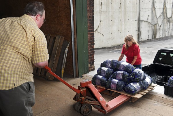 Neil Miller (left), founder and owner of Farmshed Harvest Food Hub, helps a grower unload garlic scapes at the hub's former warehouse on Burnet Avenue in Syracuse. The Farmshed hub, which relocated to the Central New York Regional Market three years ago, is closing after five years in business. (David Lassman)