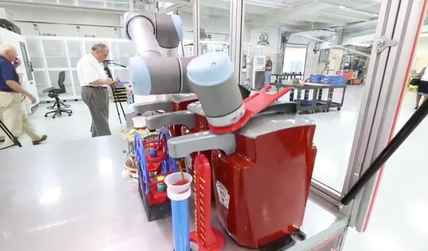 This video still from the Buffalo News shows a ketchup-dispensing robot at Staub Precision Machine in Hamburg, N.Y.