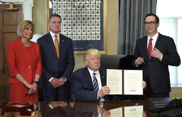 President Donald Trump shows a memorandum he signed at the Treasury Department in Washington, Friday, April 21, 2017. He invited Rep. Claudia Tenney, R-New Hartford, to witness the signing along with Sen. David Perdue, R-Ga., and Treasury Secretary Steven Mnuchin. (AP Photo/Susan Walsh)
