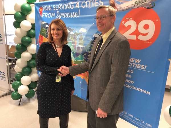 Christina Callahan, executive director of Syracuse Hancock International Airport, and Rick Zeni, chief information officer of Frontier Airlines, shake hands following the announcement in April that the low-cost carrier will offer nonstop flights from Syracuse to Denver; Raleigh, N.C.; Chicago;  and Orlando, Fla.