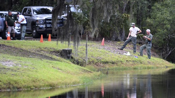 Authorities take pictures of the site where Cassandra Cline was dragged into a lagoon by an alligator and killed while trying to save her dog on Monday. (Drew Martin | The Island Packet via AP)