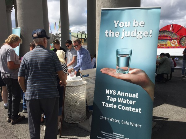 Visitors to the 2018 New York State Fair taste samples to determine which community in the state has the best tasting tap water.  (Don Cazentre)