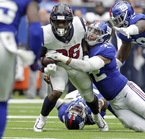 Giants defensive end Kerry Wynn, right, strips the ball away from Texans running back Lamar Miller during a game earlier this season.