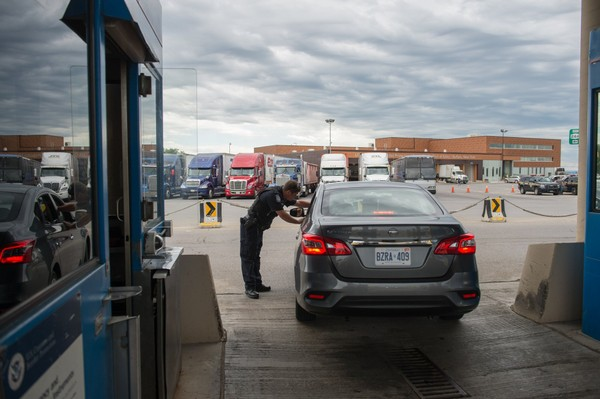 A U.S. Customs and Border Protection officer  directs a vehicle at the Peace Bridge Port of Entry in Buffalo, N.Y.