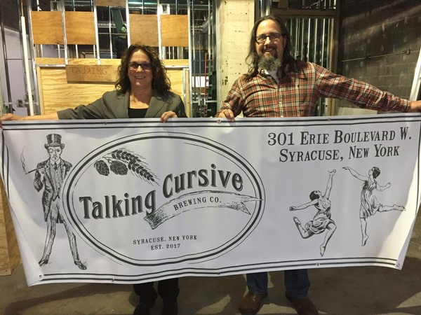 Patricia and Andrew Brooks unveil a sign for their Talking Cursive Brewing Co., a brewery/tap room they hope to open at 301 Erie Blvd. W. early in 2019.