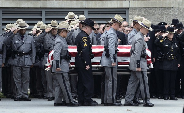 The casket of slain New York state trooper, Joel Davis, is carried out of the Magrath Sports Complex at Fort Drum, N.Y., by law enforcement personnel, during Davis's funeral service, Saturday, July 15, 2017. Trooper Davis, 36, was fatally shot July 9, while responding to reports of gunfire on a couple's property in the town of Theresa, N.Y. Police say a Fort Drum soldier, Staff Sgt. Justin Walters, fatally shot his 27-year-old wife before shooting Davis.