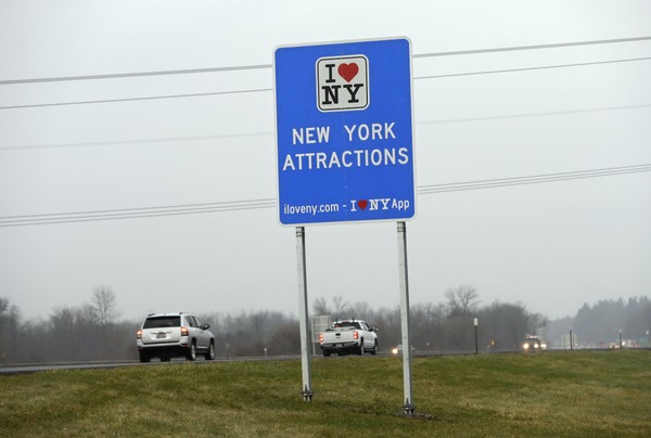 "n this Nov. 29, 2016 file photo, vehicles pass a sign proclaiming ""I Love New York"" on the New York State Thruway in Utica, N.Y."