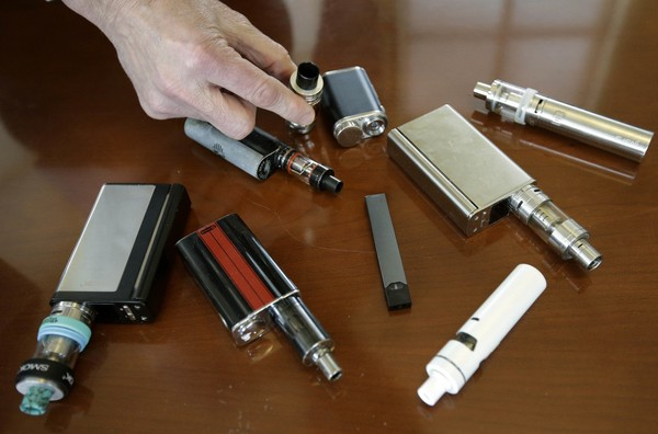 In this Tuesday, April 10, 2018, file photo, a high school principal displays vaping devices that were confiscated from students in such places as restrooms or hallways at the school in Massachusetts.