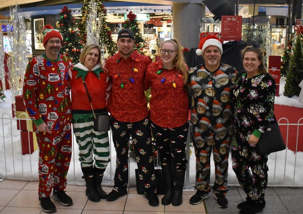 "A group of shoppers dressed up in ""ugly Christmas"" pajamas to shop on Thanksgiving at Destiny USA. The shoppers, (from left to right) Eric Wildrick, Lisa Wildrick, Garet Roik, Mattison Peet, Tom Tarry and Jodi Tarry, said they went to the mall to shop but also to have fun.  (Sarah Moses Buckshot 