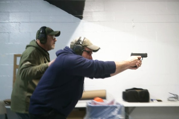 In a photo taken from a video, Mike Carnevale places his hand on the back of Mark Hennesey while instructing him at the American Tactical Systems' indoor range in Green Island, New York.