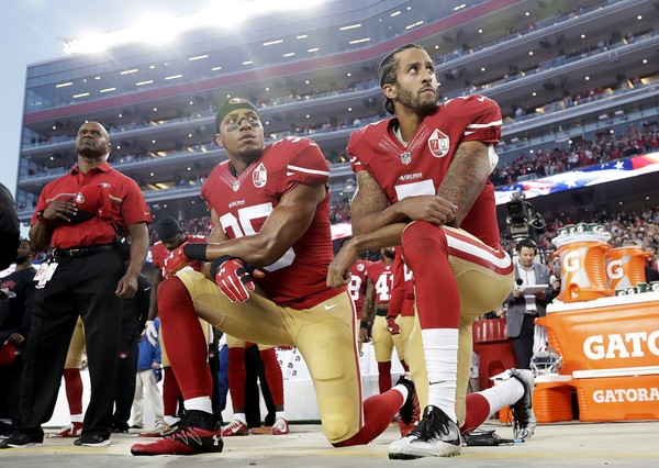Ex-49ers safety Eric Reid and quarterback Colin Kaepernick kneel during the national anthem before an NFL football game against the Los Angeles Rams in Santa Clara Calif. NFL owners have approved a new policy aimed at addressing the firestorm