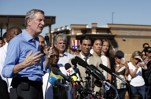 In this Thursday, June 21, 2018, file photo, New York Mayor Bill de Blasio speaks alongside a group of other U.S. mayors during a news conference outside a holding facility for immigrant children.