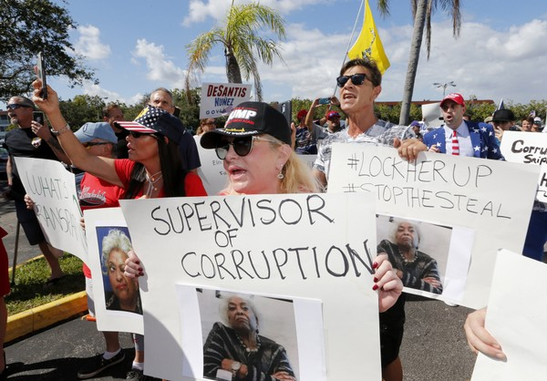 A crowd protests outside the Broward County Supervisor of Elections office Friday, Nov. 9, 2018, in Lauderhill, Fla. A recount looms in a tight Florida governor, Senate and agriculture commission race.  (AP Photo/Joe Skipper)