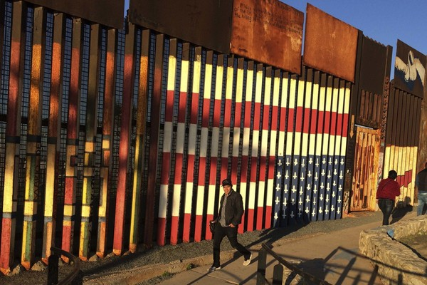 "People walk past a mural painted on a border structure in Tijuana, Mexico, on Wednesday, Jan. 25, 2017. The mural, entitled ""SOS, Deported Veterans,"" was painted in 2013 by artist Amos Gregory to help raise awareness of the plight of deported veterans. (AP Photo/Julie Watson, File)"