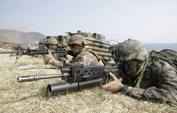In this March 30, 2015, file photo, marines of South Korea, right, and the U.S aim their weapons near amphibious assault vehicles during U.S.-South Korea joint landing military exercises as part of the annual joint military exercise Foal Eagle between the two countries in Pohang, South Korea.