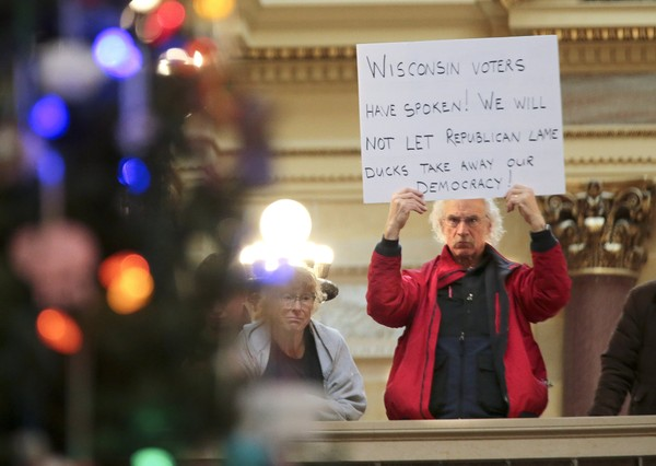 Bob Kinosian of Wauwatosa, Wisconsin, holds up a sign during the state Christmas Tree lighting ceremony in state Capitol Rotunda on Dec. 4, 2018. The Senate and Assembly are set to send dozens of changes in state law to Gov. Scott Walker's desk.