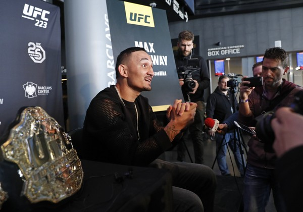 With his belt by his side, UFC featherweight champion Max Holloway speaks to reporters during UFC223's media event, Thursday, April 5, 2018, in New York. (AP Photo/Kathy Willens, File)