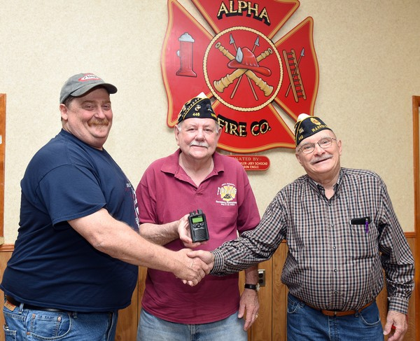 Alpha Volunteer Fire Company Chief Sean McDyer, left, shakes hands with Warren County American Legion Commander Leo Becker, right, as John Dolak American Legion Post 446 Adjutant Tom Fey, center, holds one of the new pagers purchased by the fire department with a Legion donation of $10,000.