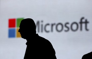 In this Nov. 7, 2017, file photo, a man is silhouetted as he walks in front of Microsoft logo at an event in New Delhi, India. Microsoft on Aug. 21, 2018, says it's uncovered new Russian hacking attempts targeting U.S. political groups ahead of the midterm elections. (AP Photo/Altaf Qadri, File)