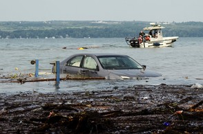 A car floats in Seneca Lake as crews attempt to drag a shed out of the water at Lodi Point in Lodi, Schuyler County.