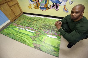 In the May 16, 2013, file photo, Attica Correctional Facility inmate Valentino Dixon poses with his golf art he creates in prison in Attica, N.Y. (AP Photo/David Duprey, File)