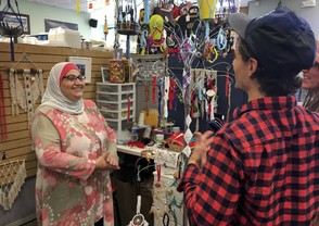 Former Iraqi refugee Nadeen Yousef, left, speaks to customers visiting her booth at the West Side Bazaar, where refugees sell clothes, crafts and food, Thursday, Sept. 27, 2018, in Buffalo, N.Y.