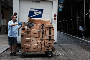 A US Postal worker delivers Amazon boxes outside of the New York Stock Exchange (NYSE) on October 11, 2018 in New York City.