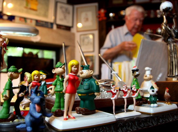 In this Aug. 16, 2010 photo, Mort Walker, the artist and author of the Beetle Bailey comic strip, stands in his studio as figurines of his most famous characters rest on his desk  in Stamford, Conn.