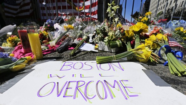 FILE  - In this April 17, 2013 photograph, flowers and signs adorn a barrier, two days after two explosions killed three and injured hundreds, at Boylston Street near the of finish line of the Boston Marathon at a makeshift memorial for victims and survivors of the bombing. Boston will mark the second anniversary of the 2013 marathon bombings Wednesday, April 15, 2015 with a subdued remembrance that includes a moment of silence, the pealing of church bells and a call for kindness. (AP Photo/Charles Krupa, File)