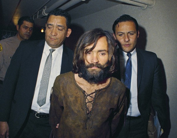 In this 1969 file photo, Charles Manson is escorted to his arraignment on conspiracy-murder charges in connection with the Sharon Tate murder case. Authorities say Manson, cult leader and mastermind behind 1969 deaths of actress Sharon Tate and several others, died on Sunday, Nov. 19, 2017. He was 83.